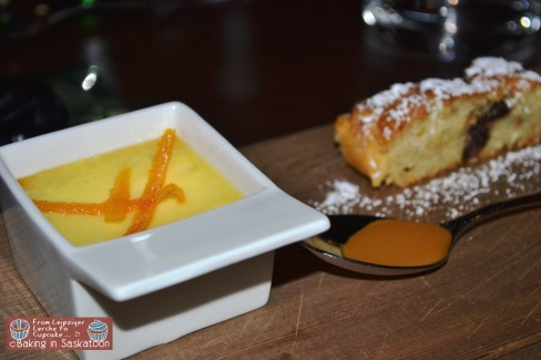 A small bowl of creme bruelee, a slice of cake and a spoon of caramel sauce.